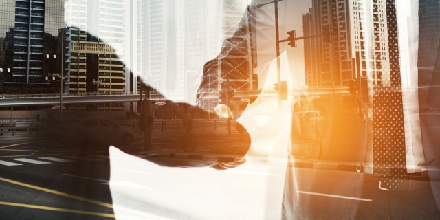 Multiple exposure shot of two businesspeople shaking hands superimposed on a cityscape